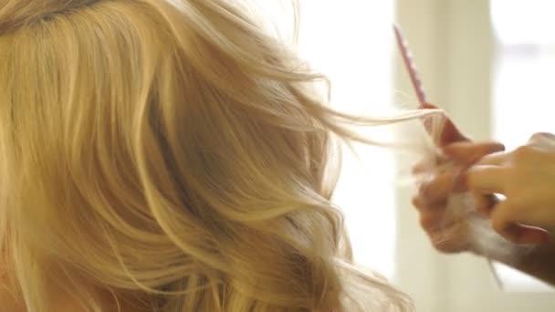 Fodrász teszi esti frizura közelről a szőke haj üzleti nő szépség szalon