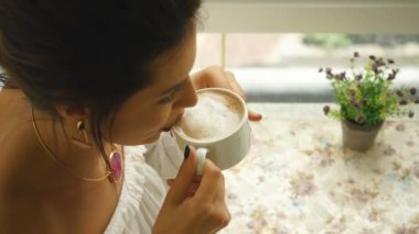 Beautiful woman in white blouse, drinking coffee in restaurant