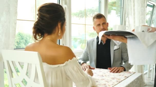 Happy waiter serving a stylish couple coffee as they sit at a table in a restaurant