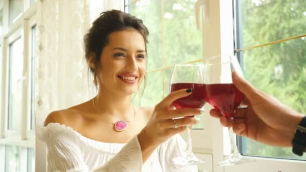 Zwei Personen mit Weingläsern toasten. junges Paar trinken Rotwein im restaurant