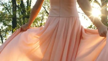 A woman walks through the woods in a dress in peach color
