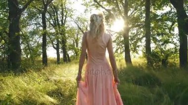 Beautiful blonde in a dress of peach-colored walks in the woods and have fun