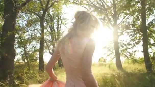 schöne Blondine in einem Kleid von pfirsichfarbenen Spaziergänge im ...