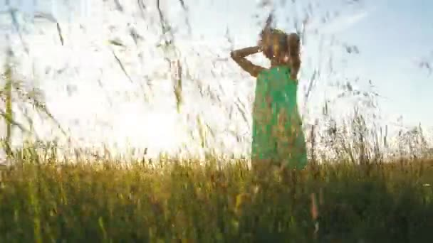 beautiful young woman walks in a light dress on the field among the ears