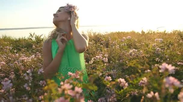 krásná středního věku blond žena. atraktivní sexy dívka v poli s květinami pózuje na kameru