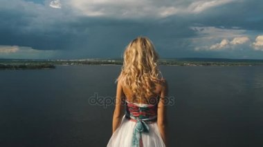 The blonde raises her arms up on the edge of a cliff,a river in the background, rear view
