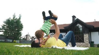 Father with his small son playing in the grass on the summer park.