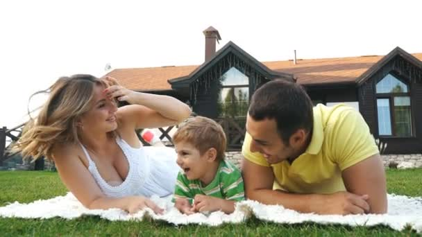 happy family lying on the grass in a park and laughs