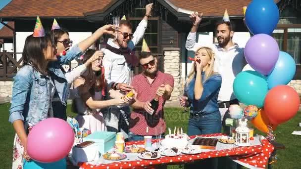 Gruppe von fröhlichen Freunden mit einer Party in der Stadt werfen Konfetti und Champagner trinken