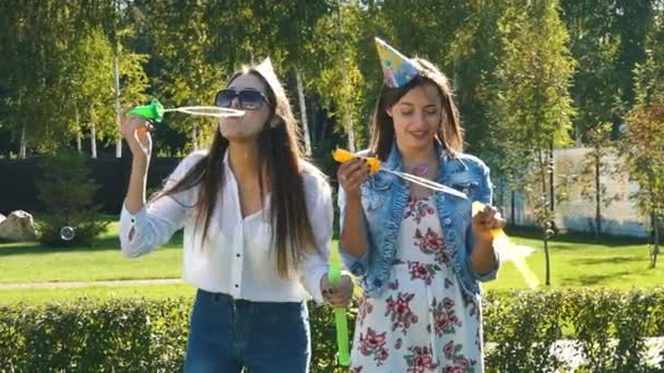 Two carefree young girlfriends having fun together blowing bubbles