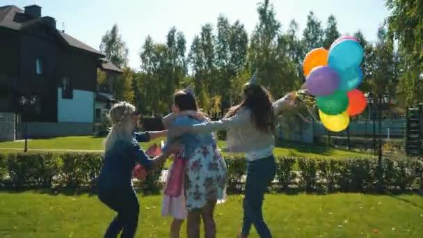 Oslavenkyně přijímá gratulace a dary od kamarádky. Všechny jsou elegantně oblečený a radostné. Veselá oslava narozenin