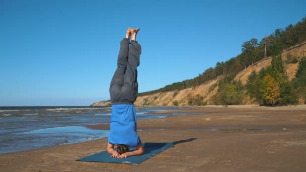 Muscular handsome young man working out, yoga, pilates, fitness training, doing handstand, Scorpion Pose