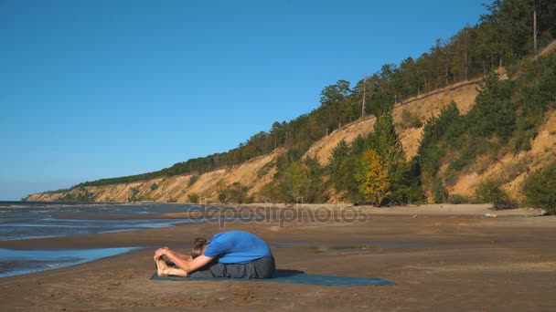 man in Lotus pose meditating at the beach