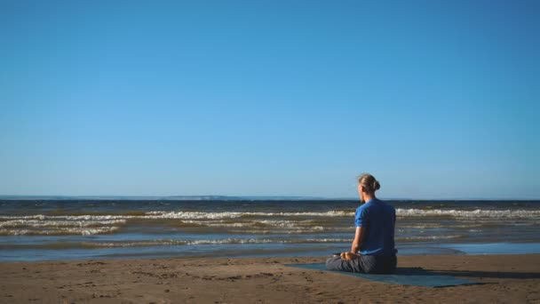 Mann in Lotus Pose meditieren am Strand