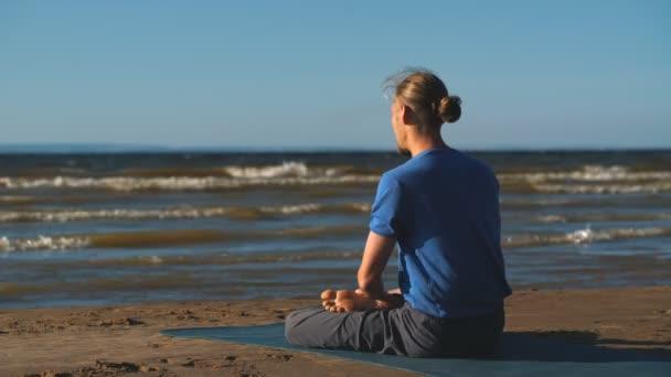 Mann in Lotus-Pose meditiert am Strand