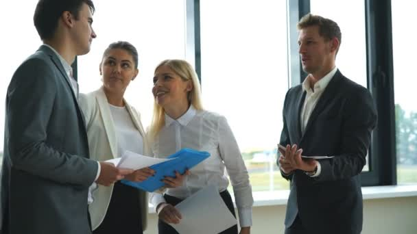 Confident business people discussing project while standing in office