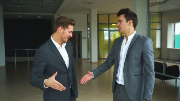 two businessmen met in the office and shake hands