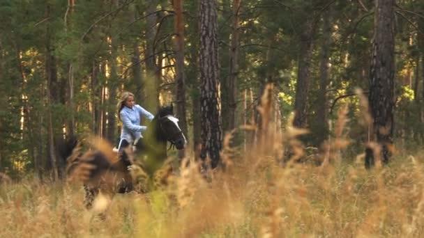 Mädchen reitet auf braunem Pferd durch den Wald