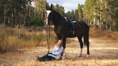 Girl blonde sitting next to the horse In wood