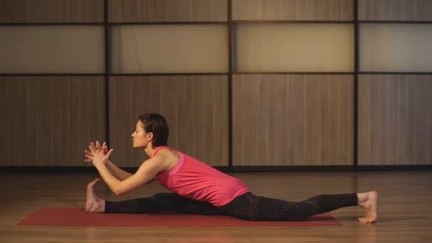 Sportive mladá dívka strečink nohou, jóga třídy. žena sedí v vlákna
