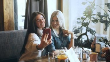 two beautiful girls are doing selfie in a cafe and smiling