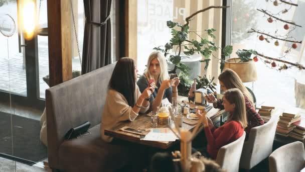 Čtyři krásné ženy sedí v kavárně s telefony