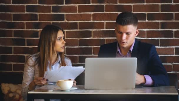 Geschäftsmann und ein Kollege diskutieren im Café über die Arbeit mit Laptop