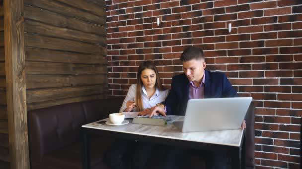 Zwei junge Geschäftsleute arbeiten in Coffeeshop am Laptop