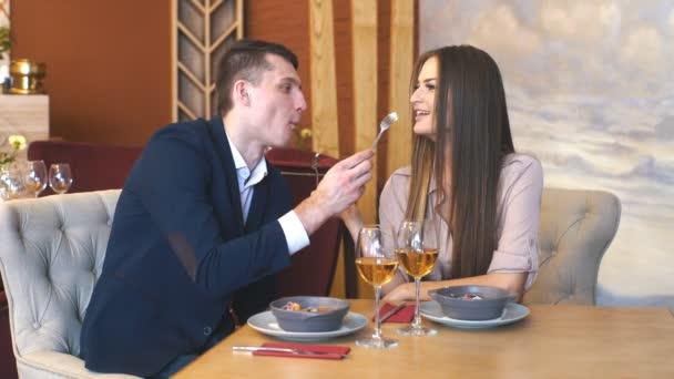 krásný mladý pár se sklenkami vína v luxusním interiéru