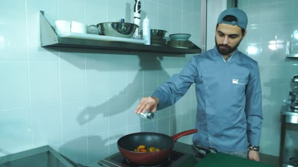 Frying pan with vegetables in chef hand. Male chef cooking vegetables at restaurant