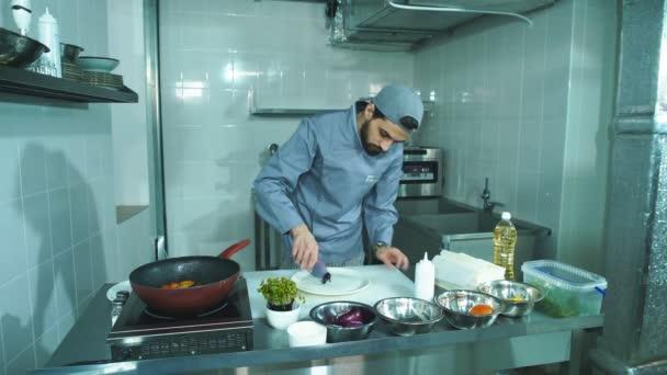 kuchař nalévá omáčka na talíři k servírování