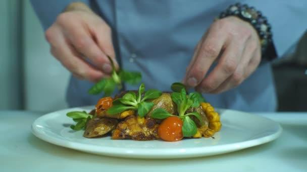 Šéfkuchař, dokončování a obloha potraviny, kterou připravil, miska s vepřovým masem a zeleninou