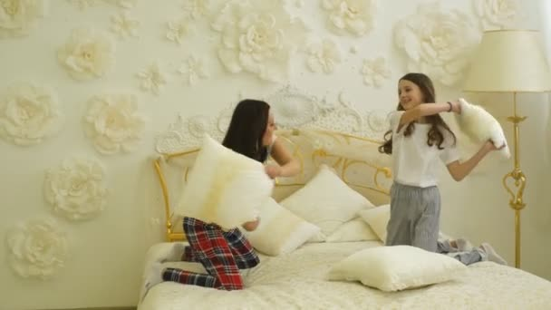 happy family mother and child daughter playing on bed and pillow fight
