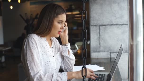 Beautiful young woman working with laptop and talking on smartphone talking to customer sitting near window