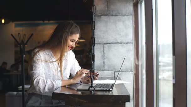 Žena na sobě bílou košili úsměv a myšlení v kavárně café s počítači laptop na stole