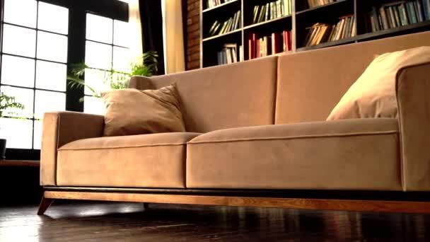 béžová kožená pohovka v interiérovém pokoji s knihovnou.