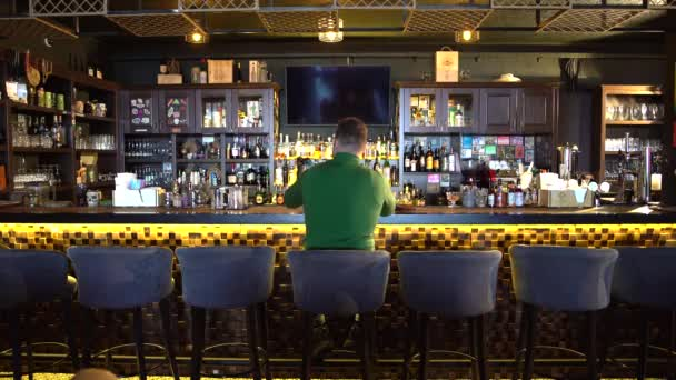 a man sits behind a bar and takes a selfie