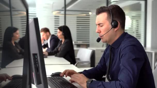 smiling man taking call in busy call center. In the background there are his colleagues also talking to clients on phone