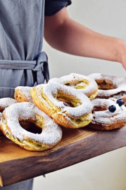 eclair rings with custard cream on grey background, selective focus