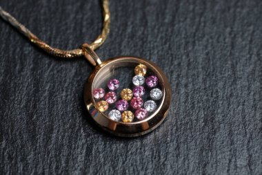 Golden pendant with colored rhinestones on a stone background. Close up.