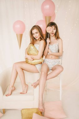 Girl in cute pink pajamas with tasty huge lollipop and ce-creams on the background. Candy party style