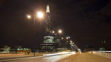 LONDON, UK - APRIL 5: Traffic cars and pedestrians on London Bridge in the night with The Shard in background on April in London, UK. long exposure, traffic light
