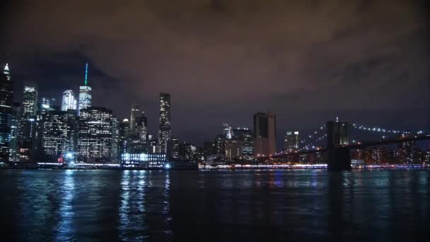 New York City városkép felhőkarcolók skyline éjszaka híd East River view Manhattan víz elmélkedés Usa keleti partján, kerület panoráma kilátás forgalom areal nézet nagy város, Időközű, 4k
