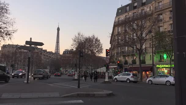 PARIS, FRANCE -circa 2017: Traffic at the crossroad with the Eiffel tower in the evening. Famous touristic places and romantic travel destinations in Europe