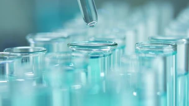 In einem Labor analysiert ein Wissenschaftler mit einer Pipette eine blaue Flüssigkeit, um DNA und Moleküle in den Reagenzgläsern zu extrahieren. Arzt arbeitet mit Flüssigkeit.