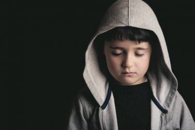 Sad boy on black background