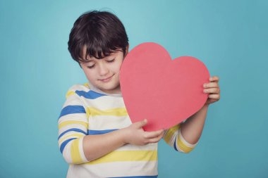 smiling boy with a heart on blue background