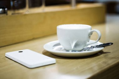 Coffee cappuccino in white cup and white mobile phone on the table in a cafe.