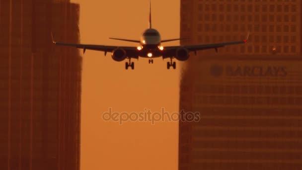 Letiště London City - velké dopravní letadlo přistání během zlaté hodiny v Canary Wharf v pozadí