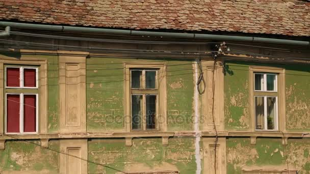 Ultra telephoto shot of an old ruined house with dormers resembling human eyes in the town of Sibiu, Transylvania, Romania